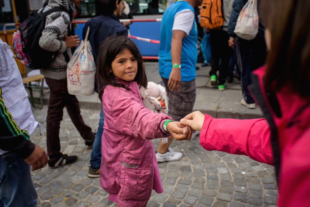 A woman gives some euro coins to a refugee child, who has arrived by train at the central station in Munich, southern Germany on Saturday, Sept. 5. Since Saturday more than 7,000 Arab and Asian asylum seekers surged across Hungary's western border into Austria and Germany following the latest erratic policy turn by Hungary's immigrant-averse government.
