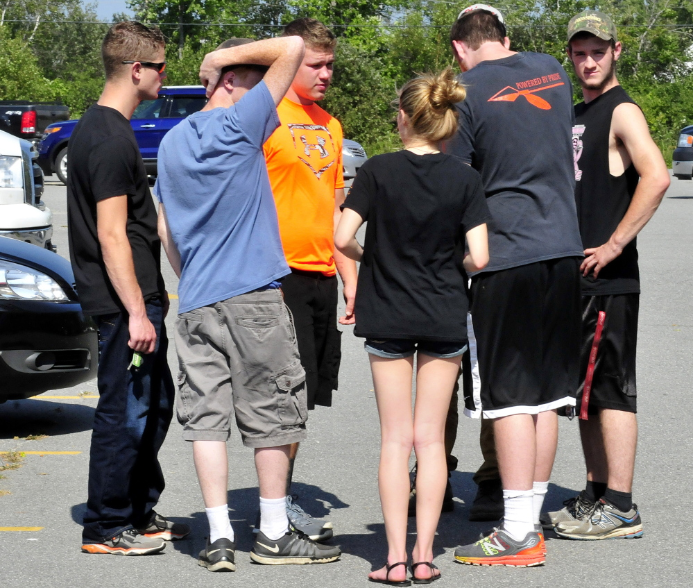 Friends, classmates and members of the Skowhegan Area High School football team gather on Monday outside the school after a memorial service for student Scott Brown, who died Sunday evening while swimming in Embden Pond in Embden.