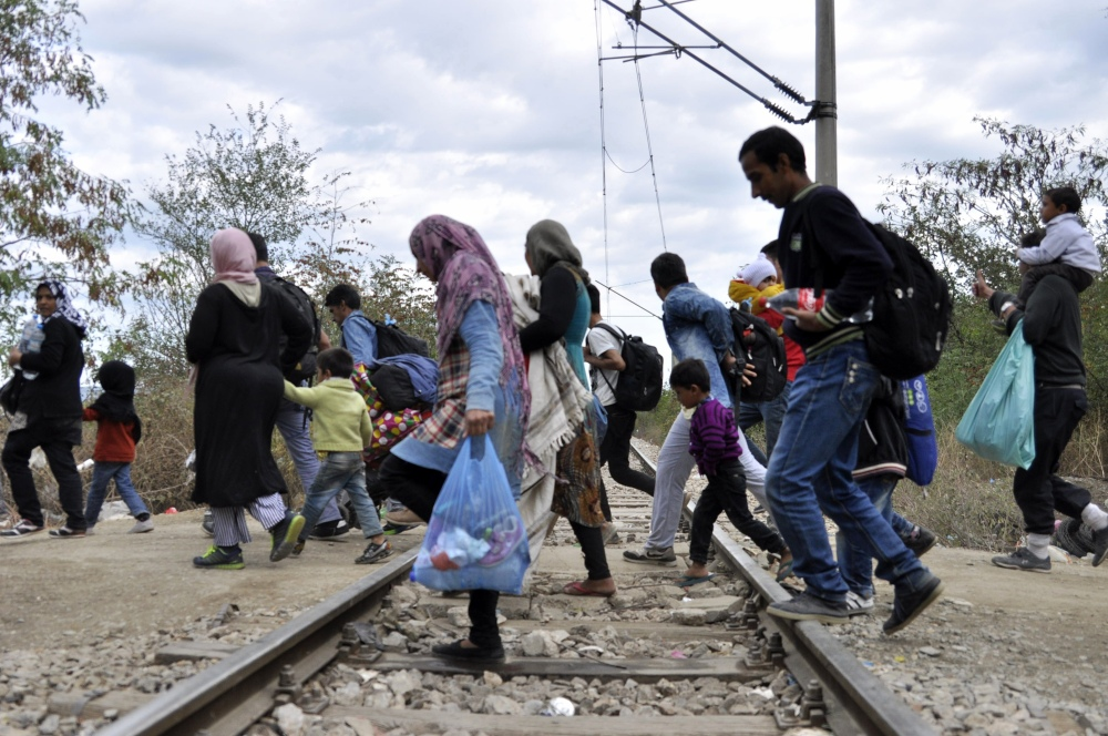 People pass railway tracks as they approach the southern Macedonian town of Gevgelija,Tuesday.