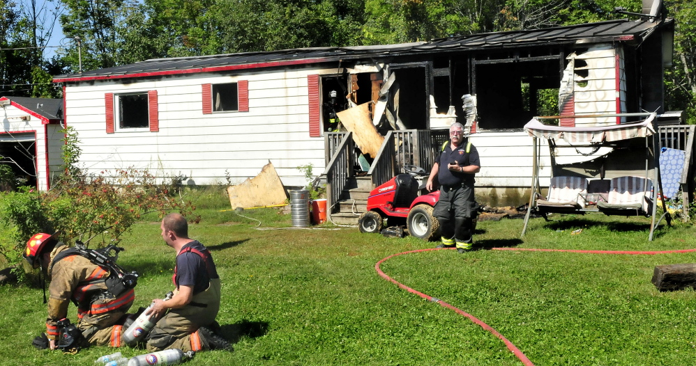 Skowhegan firefighter Linwood Corson walks out of the remains of the Main Street, Canaan, home that burned Sunday, as firefighters replace oxygen tanks at the scene where fire destroyed the home on Main Street in Canaan on Sunday.