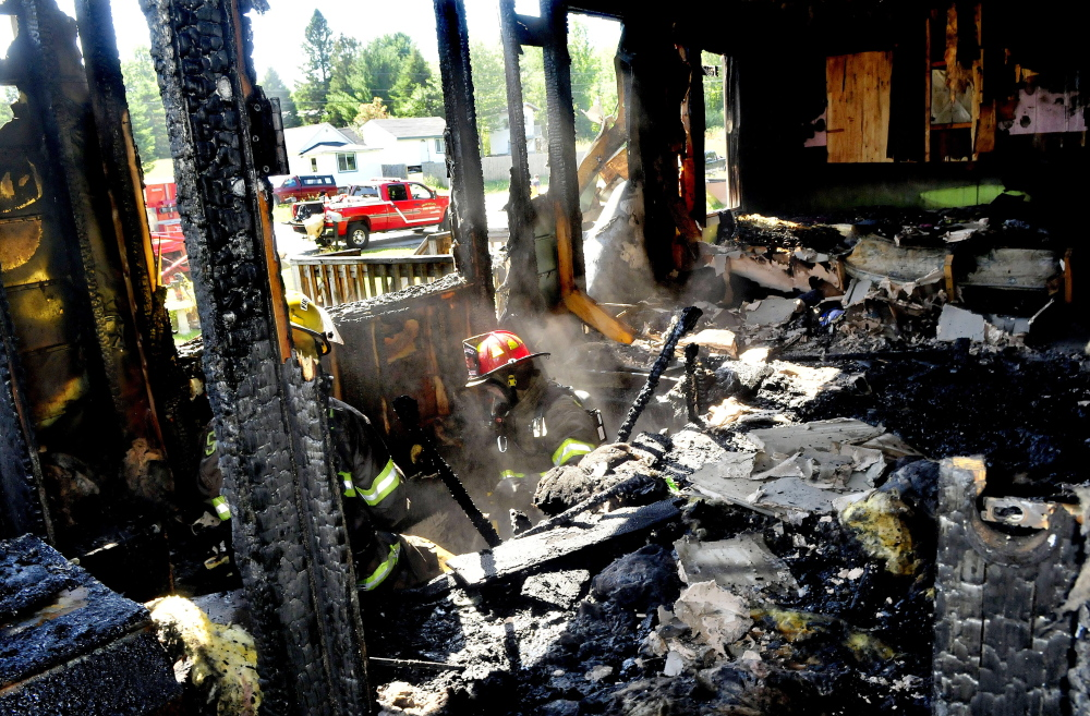 Two firefighters extinguish fire in the floor as smoke rises from the living room of a home that was destroyed by fire on Main Street in Canaan on Sunday. The home's owners, Tanya and David McGregor, hope to rebuild, said Canaan Fire Chief Troy Bowden.