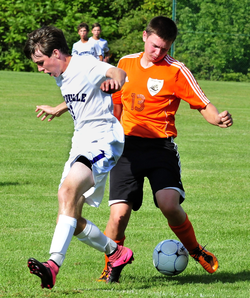 Staff photo by David Leaming   Waterville's Ethan Cayer, left, and Winslow's Hunter McCaslin scramble for the ball  during a game Tuesday at Webber Field in Waterville.