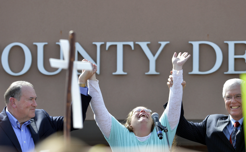 Rowan County Clerk Kim Davis, center, with Republican presidential candidate Mike Huckabee, left, and attorney Mat Staver, founder of the Liberty Counsel, the Christian law firm representing Davis, at her side, cries out after being released from the Carter County Detention Center, Tuesday in Grayson, Ky.