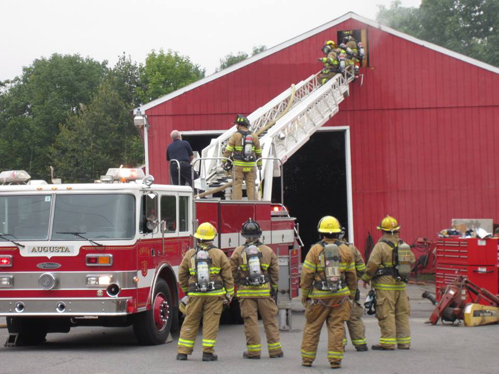"Augusta firefighters tackle a ""stubborn"" fire that started Wednesday morning in the attic of Kramer's Inc. tractor dealership on West River Road in Sidney."