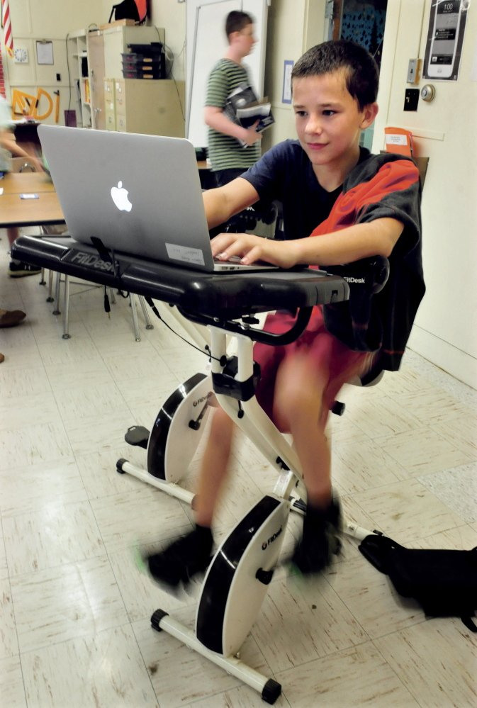 China Middle School student James Hardy pedals a bike while working on his laptop during math class on Wednesday. Hardy said he enjoys using the bike for both exercise and relaxation.