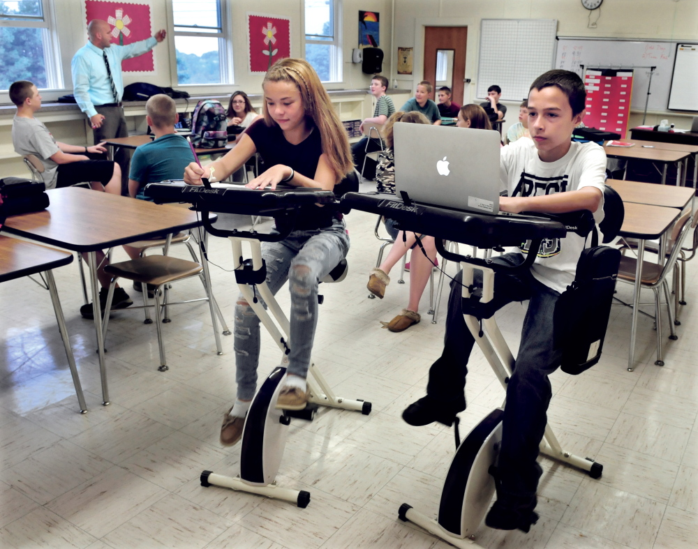 China Middle School eight grade students Morgan Presby and Colby Marston study and pedal at thier bike desks as teacher Josh Lambert leads the class on Wednesday.