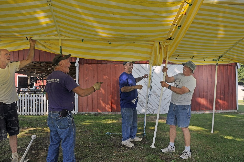 Volunteers getting ready for the Litchfield Fair erect a canopy Wednesday.