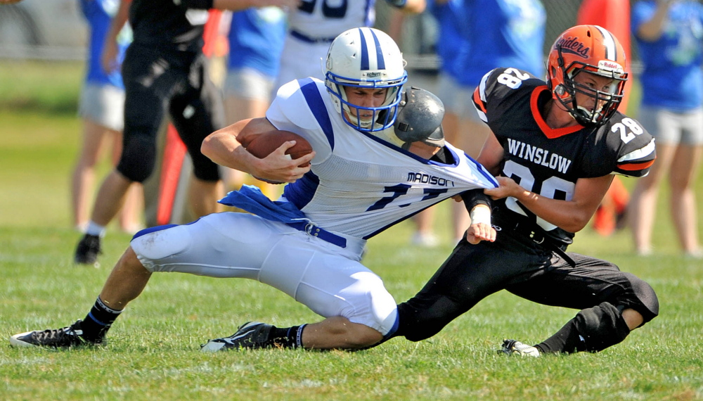 Staff Photo by Michael G. Seamans Madison quarterback Chase Malloy tries to elude a Winslow's Luke Frddette during a game last Sept. 6 in Winslow.