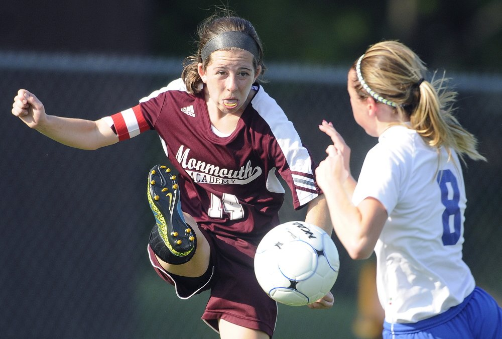 Staff photo by Andy Molloy   Monmouth Academy's Taylor Spadafora, left, kicks the ball away from Oak Hill's Rylea Mae Swan during a Mountain Valley Conference game Wednesday afternoon.