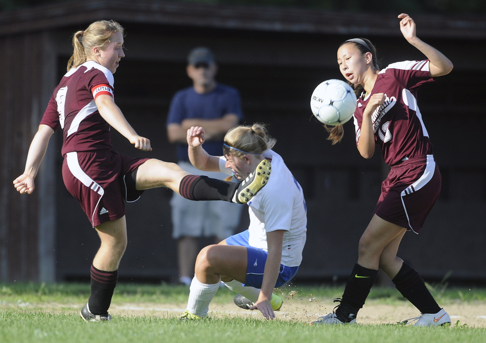 Staff photo by Andy Molloy   Monmouth Academy's Maddie Bumann, left, kicks the ball away from Oak Hill's Brittany Marquis toward Monmouth teammate Tia Day during a Mountain Valley Conference game Wednesday in Wales.