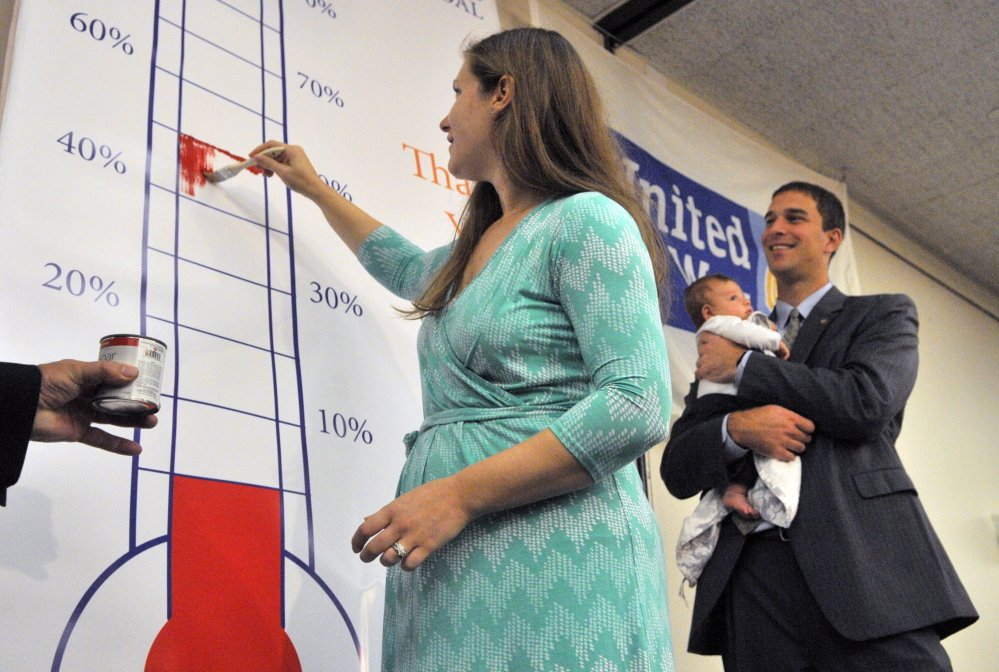 Campaign co-chairwoman Stephanie, Garofalo, left, paints in a thermometer showing they're already at 51% of their goal as co-chairman Craig Garofalo watches with their son Weston during the United Way of Kennebec Valley kickoff breakfast on Thursday at the Augusta Civic Center.