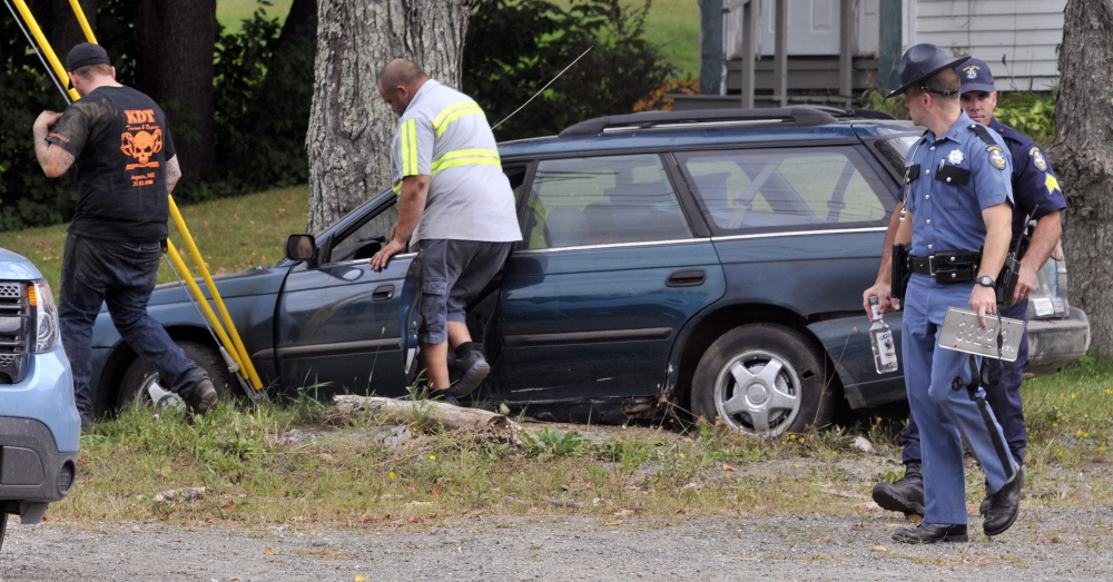 Tow truck drivers prepare to move a crashed car as  State Police Troopers walk away from a crashed car on Thursday on Leighton Road in Augusta.