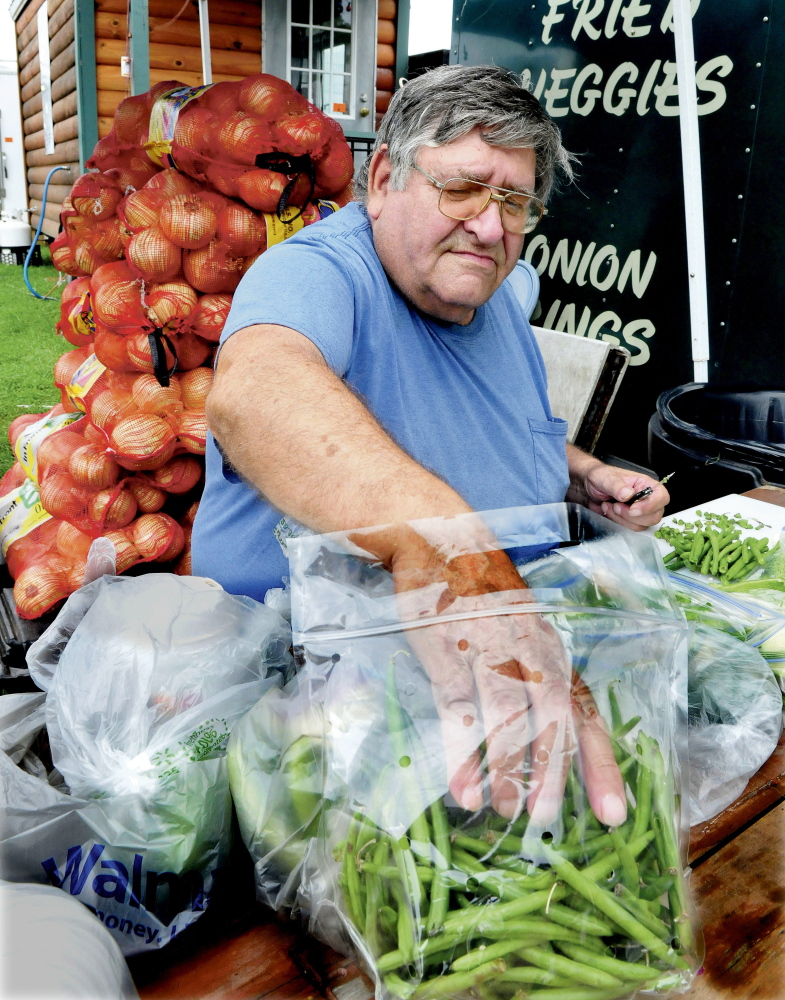 Glenn Tripp prepares vegetables at the J.H. Concessions blooming onion stand at the Clinton Lions Club fair on opening day Thursday. The fair runs through Sunday.