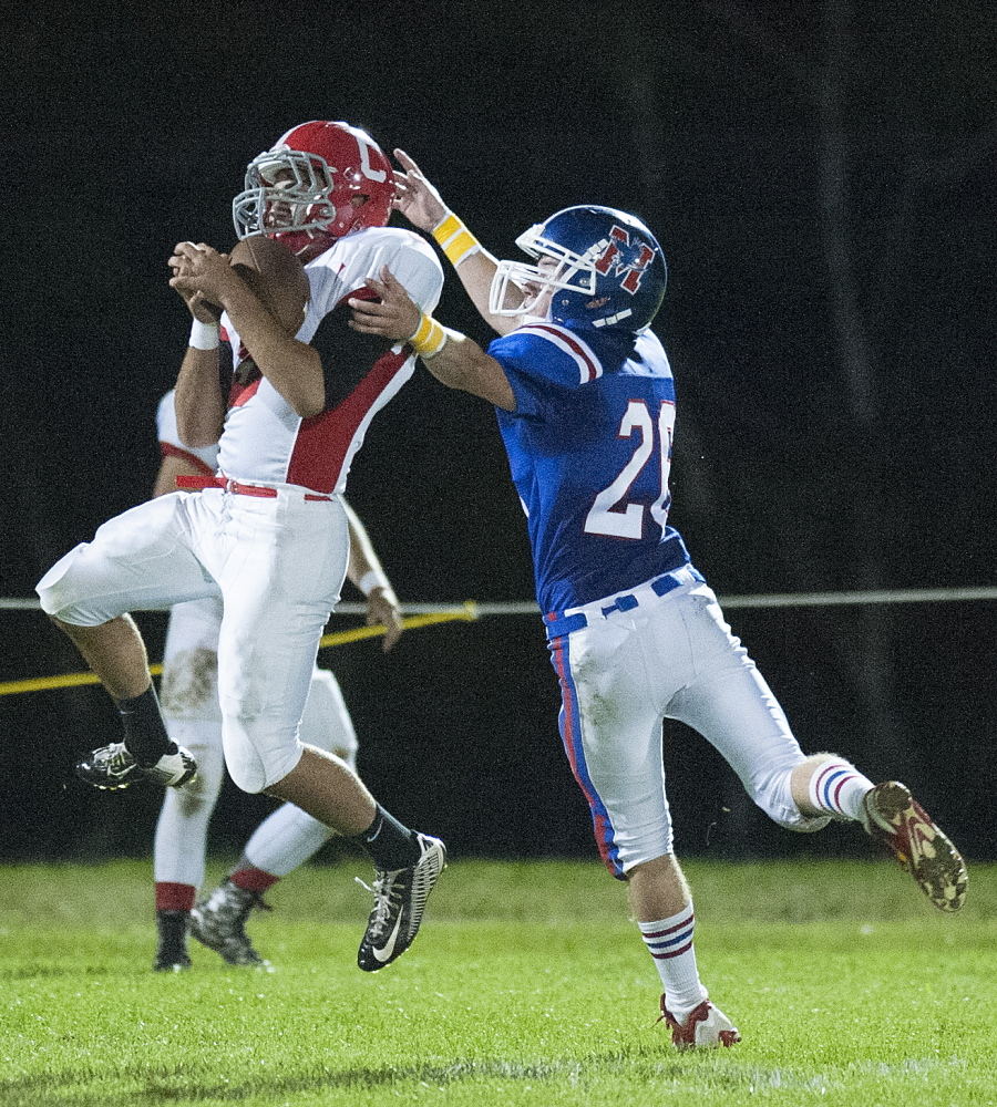 Kevin Bennett photo   Cony receivers Joey Younes, left, catches a pass under pressure from Messalonskee's CJ Gordon during the second quarter of a Pine Tree Conference Class B game Friday night at Veterans Field in Oakland.
