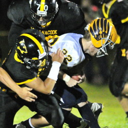 Maranacook's Jordan Sansaricq, left, and Hunter Tims, top, wrap up Boothbay's Xavier Downing during a Campbell Conference Class D game Friday night at Ricky Gibson Field of Dreams.
