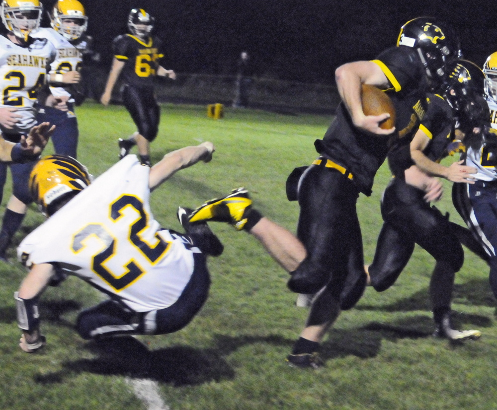 Maranacook quarterback Kyle Morand, right, runs past Boothbay's Xavier Downing, left, en route to the end zone during the second quarter of a Campbell Conference Class D game Friday night at Ricky Gibson Field of Dreams in Readfield.