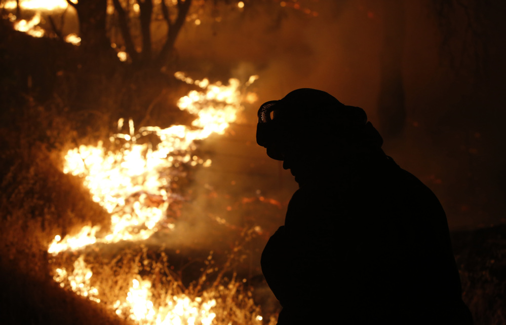 A firefighter turns his head from the flame of the Butte Fire burning near San Andreas, California, on Friday.
