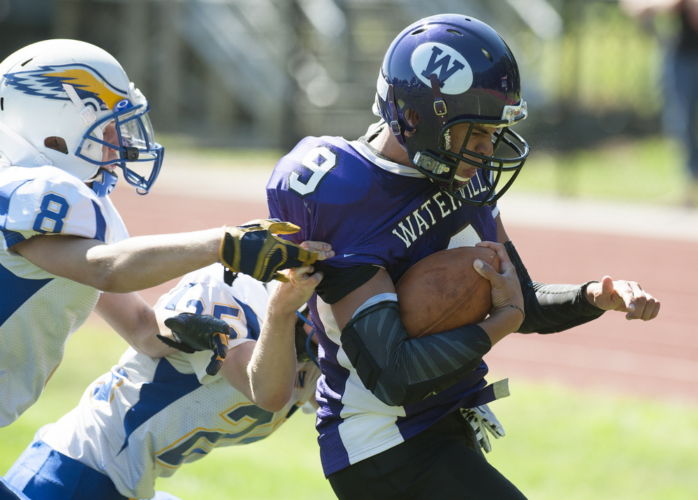 Kevin Bennett photo   Waterville's Demetrius Ramirez manages to score a touchdown despite the pressure from Hermon defenders Tyler Carmichael, left, and Jacob Baily during the first quarter Saturday afternoon.
