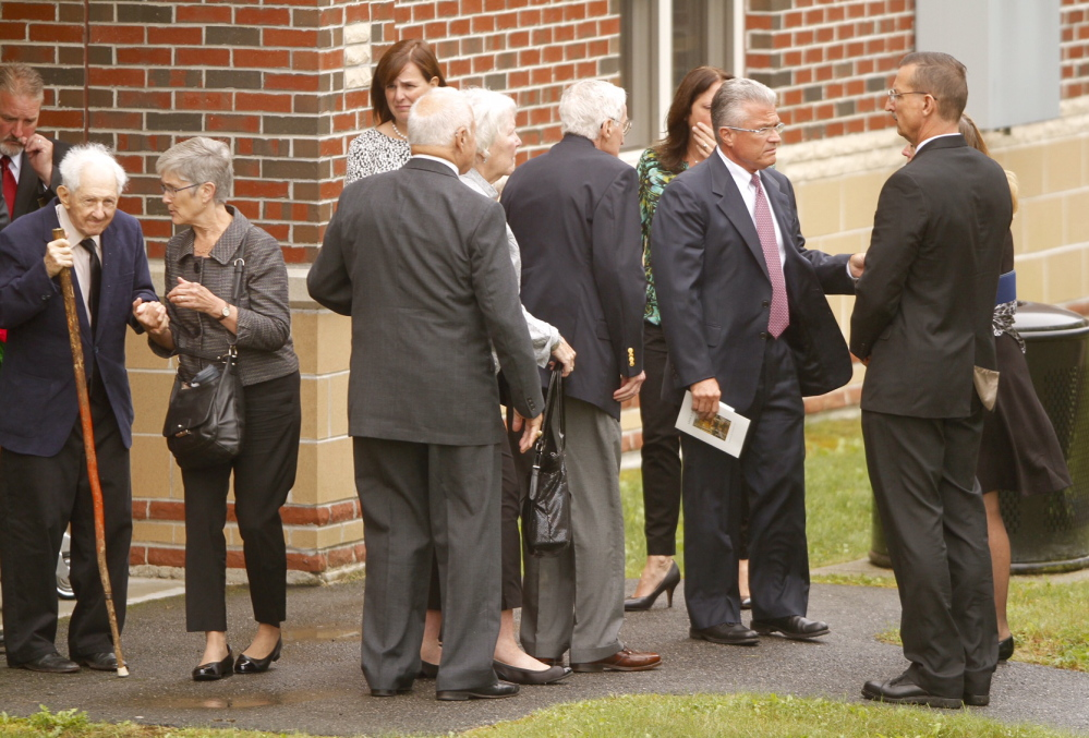 Members of former L.L. Bean leader Leon Gorman's funeral, including current CEO Christopher McCormick, second from right, gather after Gorman's memorial service at the Westbrook Performing Arts Center on Sunday.