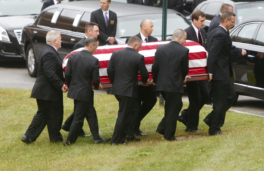 Pallbearers carry the flag-draped casket of former LL Bean leader Leon Gorman from his memorial service at the Westbrook Performing Arts Center on Sunday.