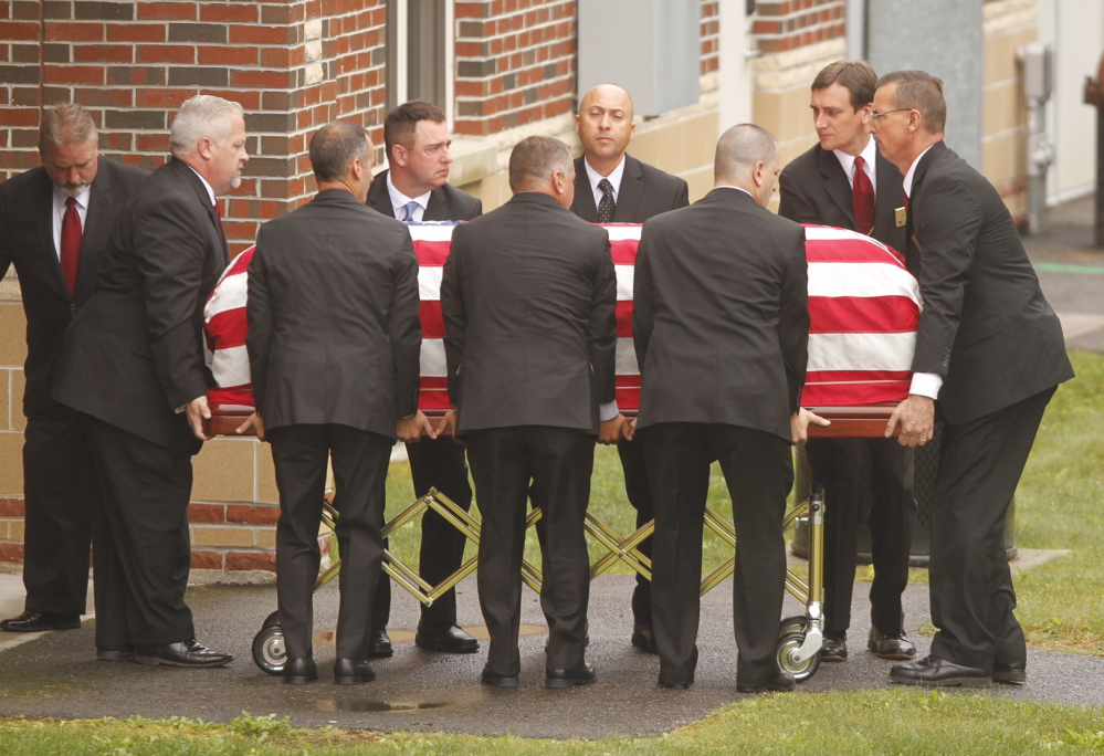 The flag-draped casket of former L.L. Bean leader Leon Gorman is carried by pallbearers from his memorial service at the Westbrook Performing Arts Center on Sunday.
