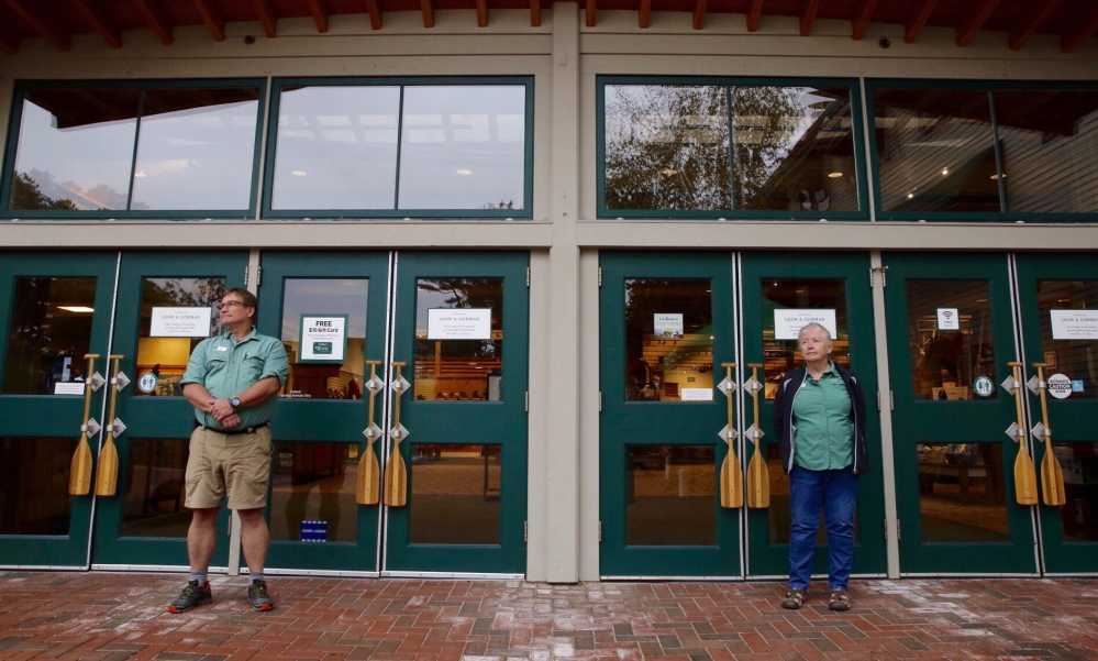 Longtime employees Mark Phillips and Marilyn Lucey stand at the entrance to L.L. Bean's flagship store in Freeport. The store is closed Sunday from 8 a.m. to noon in memoriam of Leon A. Gorman, who died Sept. 3.