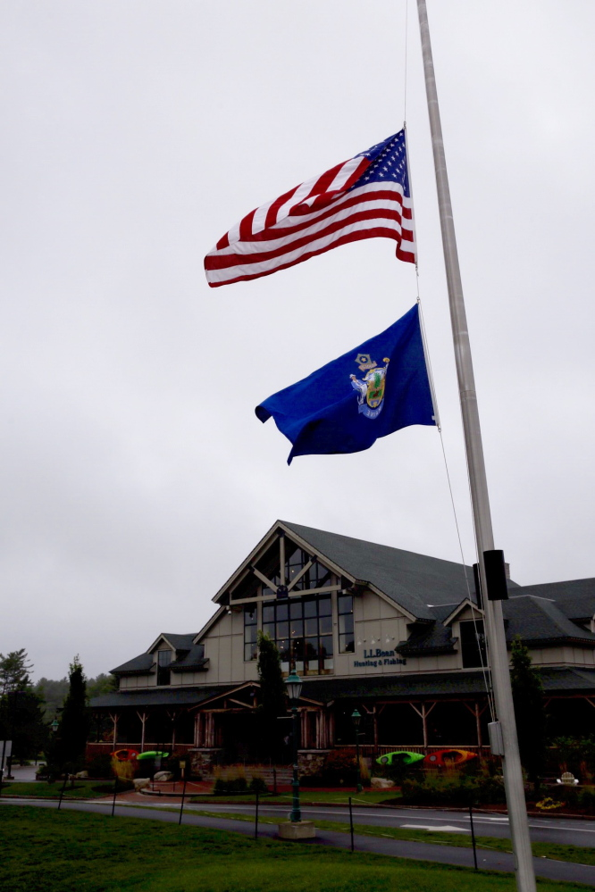 Flags fly at half-staff Sunday at the L.L. Bean flagship store in Freeport.