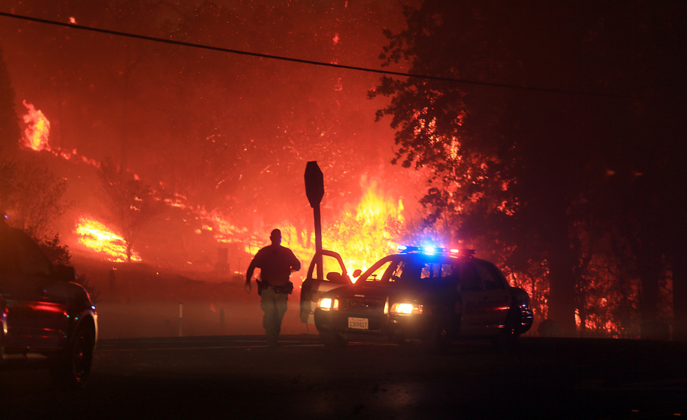 Lake County sheriff's officers  prepare to evacuate Butts Canyon Road in Middletown, Calif., as the Valley  fire jumps Hwy 29, on Saturday.