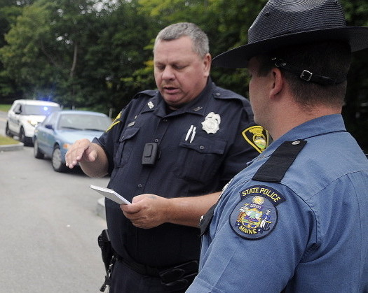 Gardiner Police Officer Eric Testerman, left, shares information with State Trooper Randy Hall Sunday on the Kennebec River Rail Trail in Farmingdale about a suspect involved in an assault on the trail. A man was transported to the hospital by ambulance following the assault that occurred before 10 a.m. across from Sheldon Street, police said.