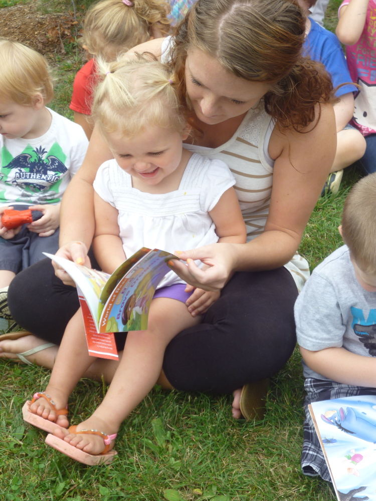 Charli Cote reads her new book with Educare staff member Leeannza Delosh.
