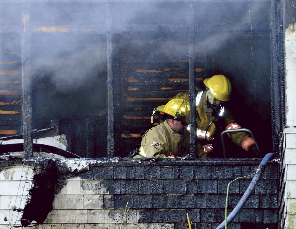Firefighters can be seen putting out fire inside a home that was destroyed on Swan Hill Road in Oakland on Monday.