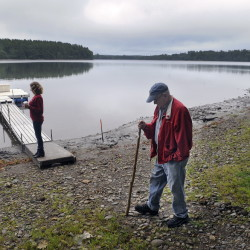 Stan Whittier walks on the shore of Clary Lake in Jefferson last month while his daughter, Jane Roy, stands on the family's dock. It's been nearly three years since property owners around Clary Lake in Jefferson and Whitefield appealed to the state to intervene over a low water level, and residents say the situation still hasn't improved.