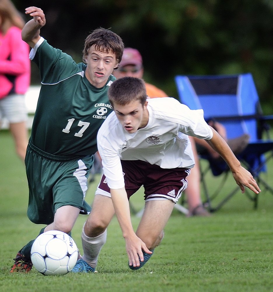 Staff photo by Andy Molloy Monmouth Academy's Gage Cote, right, and Carrabec High School's Jarrod Daigle scramble for the ball during a soccer game Monday in Monmouth.