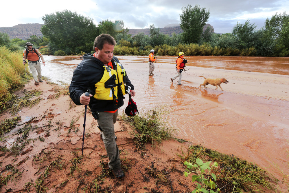 Members of the Mojave County search and rescue team use dogs to search for bodies after a flash flood Tuesday in Colorado City, Ariz.