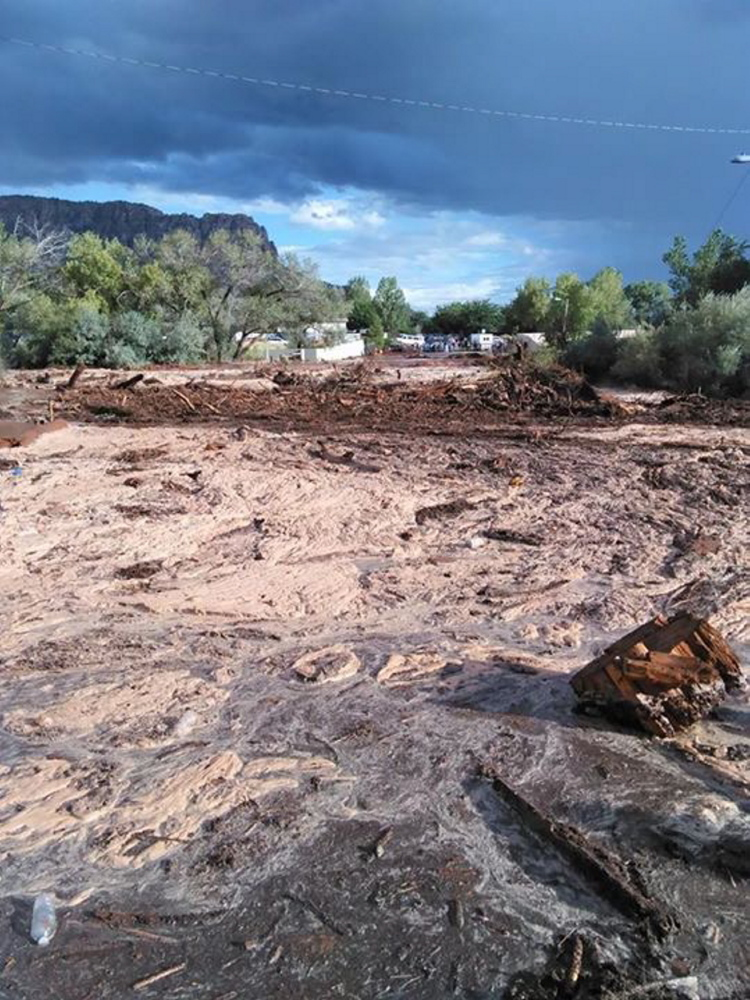 Debris and water cover the ground after a flash flood Monday in Hildale, Utah. Authorities say multiple people are dead and others missing after a flash flood ripped through the town on the Utah-Arizona border Monday night.