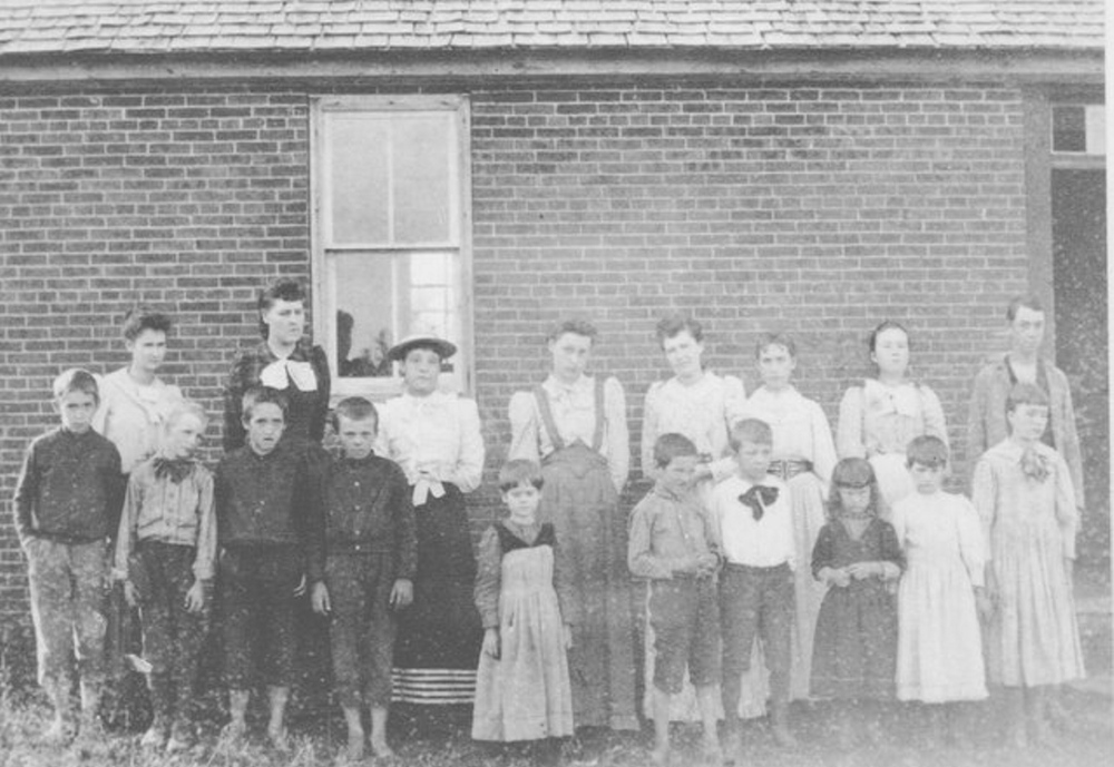 Photo of students taken in 1891 at the brick Bond School on East Pond Road, Jefferson. Front, from left, are Frank Nash, Will Meservey, Fred Nash, Henry Chesam, Eva Hall, Bert Ward, Harry Vinal, Addie Nash, Fannie Nash and Ella Hall. Back, from left, are Edith Flagg, Adelia Richardson-teacher, Jennie Hall, Inez Hall, Emma Flagg, Estelle Nash, Margaret Hall and Forest Moody.