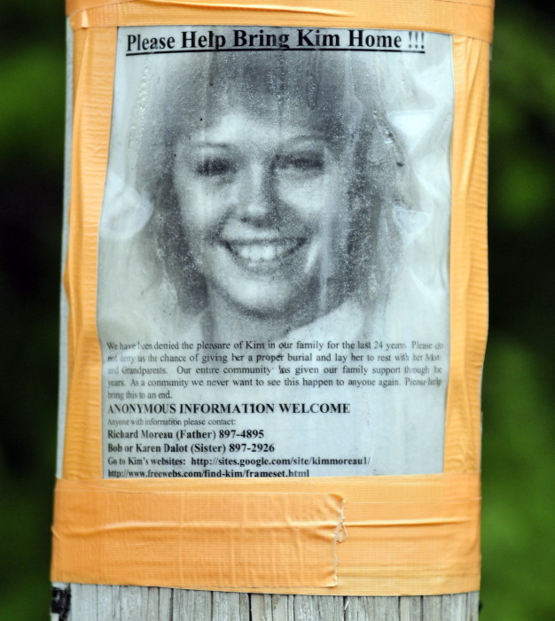 A poster of Kimberly Moreau hangs on utility pole across street from a police search scene on Aug. 7 in Canton.