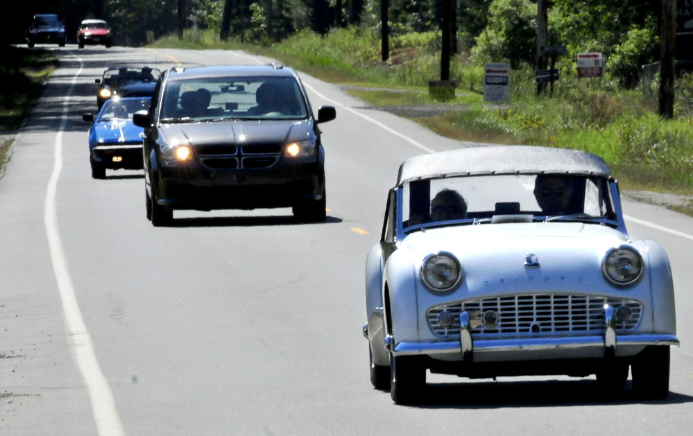 Allan McClure of Winslow drives his 1960 Triumph TR3A as other participants of a British car touring group follow — interrupted by a very non-British Chrysler van — on Route 8 in North Belgrade to resident Steve and Janet Towle's home on Tuesday. The group was traveling from Nova Scotia to Stowe, Vermont.