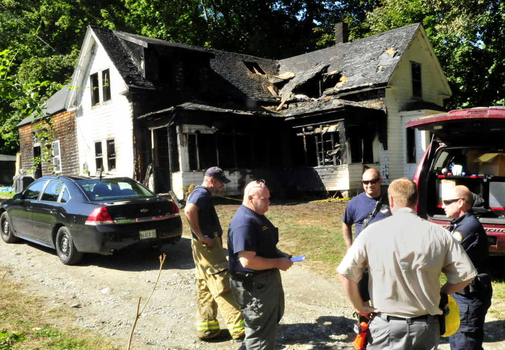 Oakland fire chief Dave Coughlin, left, listens as State Fire Marshal's Office investigator Kenneth MacMaster speaks with other investigators including John Wardwell, second from right, and Jeremy Damren outside the fire damaged home on Swan Hill Road in Oakland on Tuesday to determine the cause of the Monday fire.
