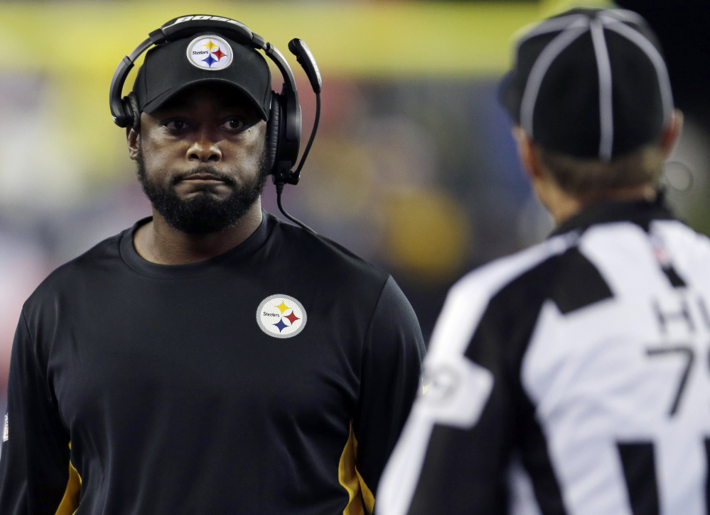 Pittsburgh Steelers head coach Mike Tomlin, center, talks to  head linesman Kent Payne, right, in the first half of a game last week against the New England Patriots in Foxborough, Mass.