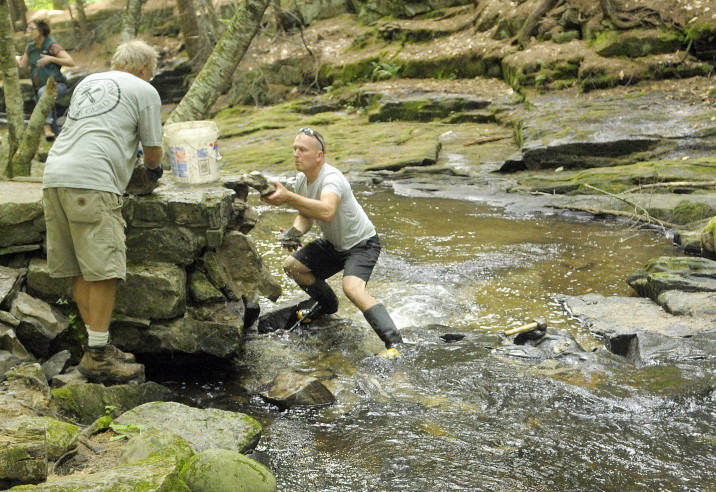 Dan Ucci, owner of Ledge Hill Creations Inc., left, and Lance Carlezon pick up fallen rocks in July after taking down a small arched bridge in Vaughan Woods in Hallowell. The bridge was built in 1900 by William Warren Vaughan and his son Sam Vaughan and local masons.