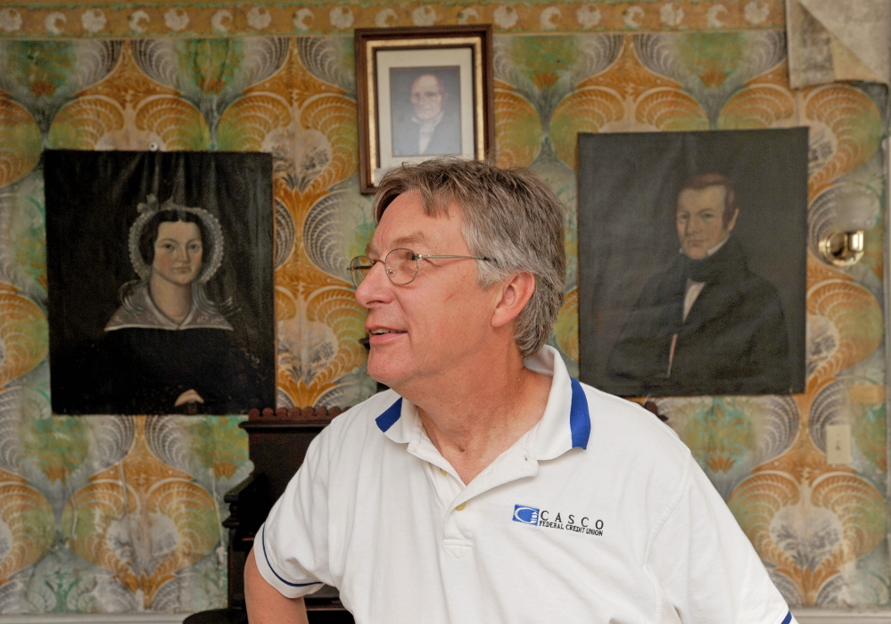 Peter Weston stands in front of pictures of relatives, Deacon Ben Weston, top picture, Nathan Weston, right picture and Almeda Weston, left picture, during a tour of the Weston Homestead in Madison in July 2014. Peter Weston, the 4th generation descendant of Benjamin Weston who built the homestead in the early 1800s, has the piece of history up for sale.