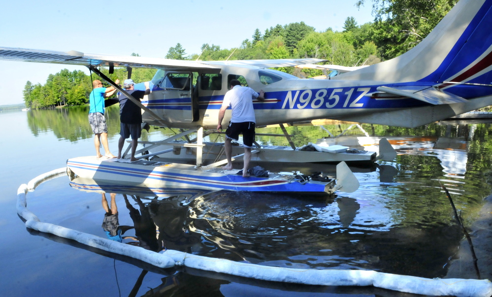 Pilot Don Stoppe, left, opens the engine compartment to his plane that was forced to land abruptly after engine failure on Wesserunsett Lake in East Madison on Thursday. Helping is passenger Perry Bryant as Stoppe's brother and passenger Rick Stoppe gets on past oil containment pads in the water.