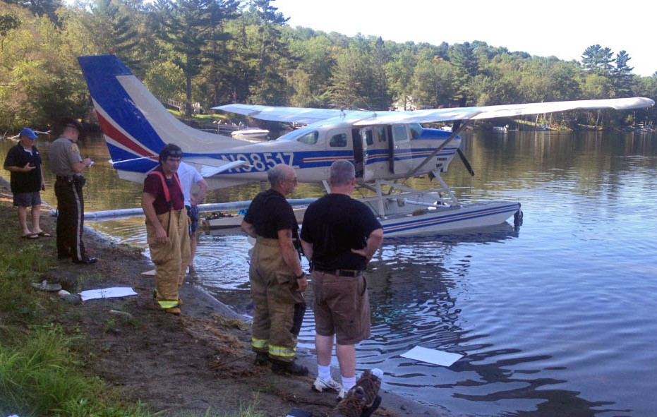Emergency responders gather around an airplane that made an emergency landing on Wesserunsett Lake Thursday morning.