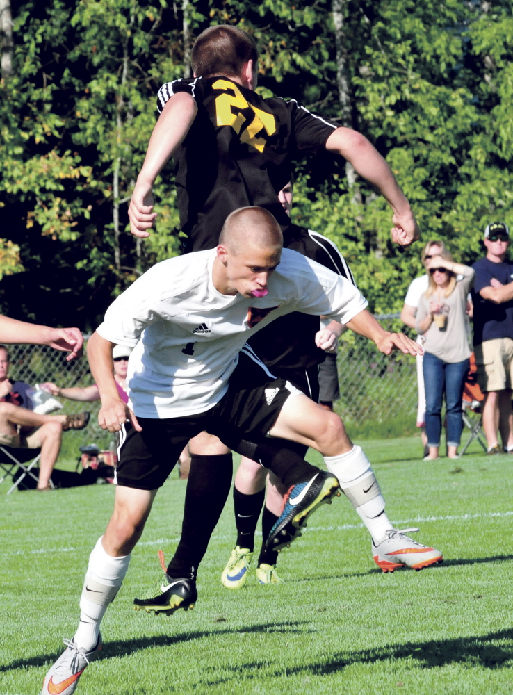Staff photo by David Leaming   Winslow's Noah Dugal, front, and Maranacook's Mark Buzzell collide during a game Thursday in Winslow. Maranacook won 2-1.