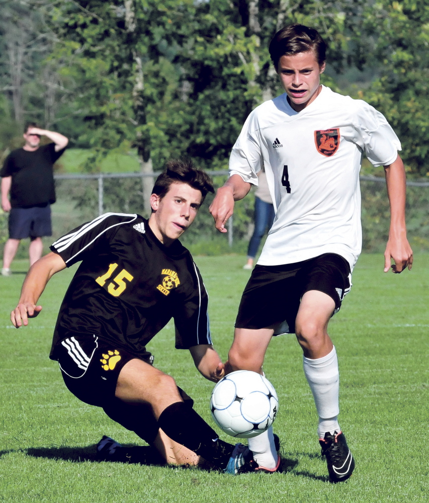Staff photo by David Leaming   Maranacook's Carlo Bozzola, left, and Winslow's Spencer Miranda compete possession during a game Thursday in Winslow.