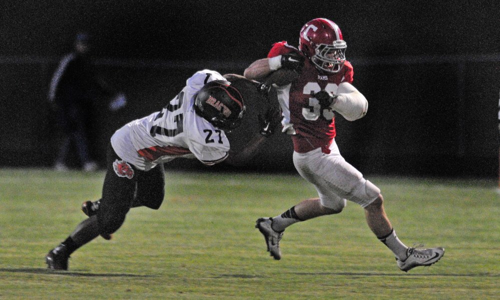 Staff photo by Joe Phelan   Brunswick defender Ben Palizay, left, chases down Cony running back Reid Shostak  during a Pine Tree Conference Class B game Friday night at Alumni Field in Augusta.