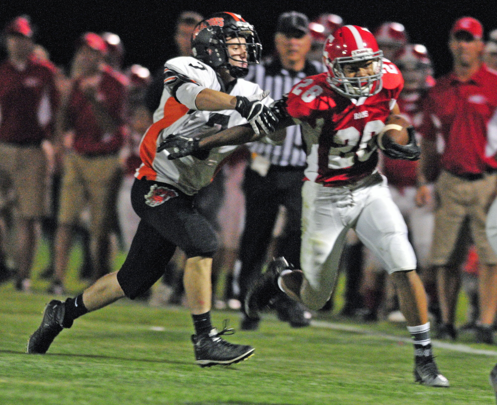 Staff photo by Joe Phelan   Brunswick linebacker Jesse Deveraux, left, catches up to Cony wide receiver Jordan Roddy at the end of a long pass play during a Pine Tree Conference Class B game Friday night at Alumni Field in Augusta.