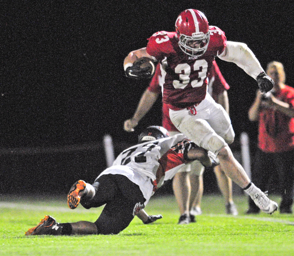 Staff photo by Joe Phelan   Brunswick defensive tackle Sullivan Boyd, left, misses Cony running Reid Shostak  during a Pine Tree Conference Class B game Friday night at Alumni Field in Augusta.