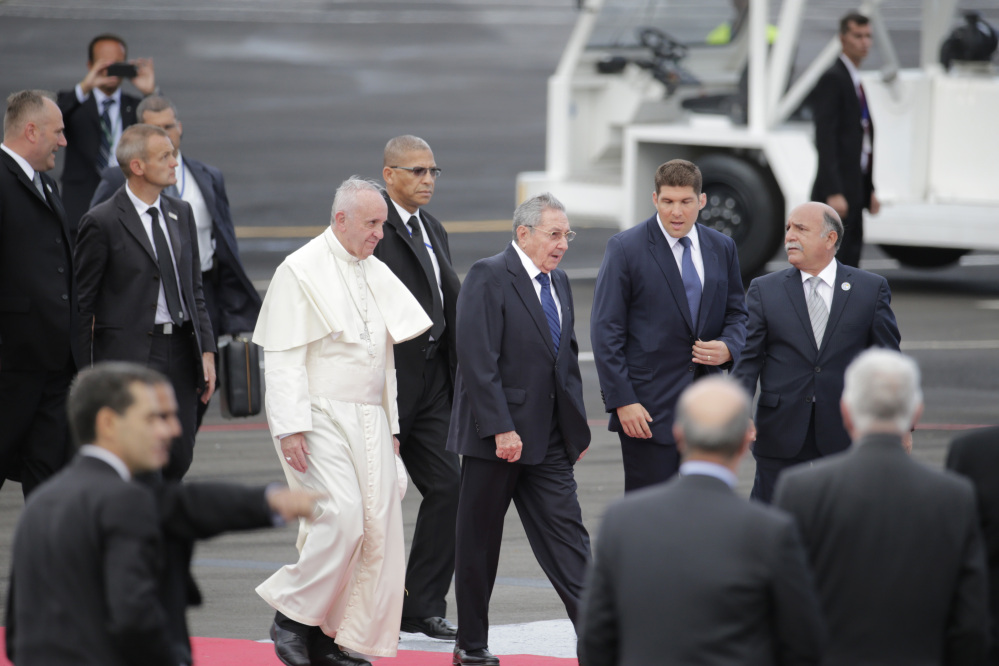 Surrounded by security, Pope Francis walks with Cuba's President Raul Castro as he arrives to Havana, Cuba, Saturday.